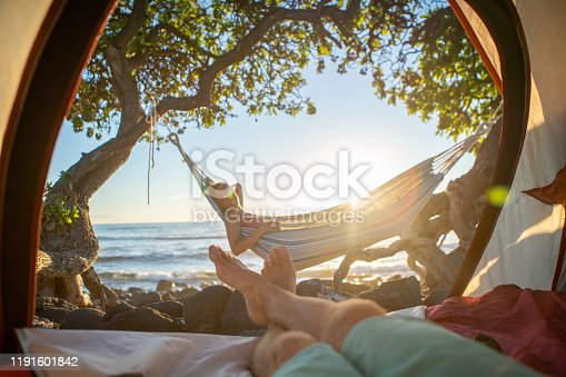 910783248 istock photo Point of view of man's feet from inside a tent camping on the beach in Hawaii looking at girlfriend in hammock outdoors 1191601842