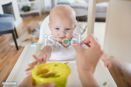 istock Point of view of mom feeding her baby with a spoon 859936596