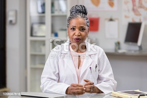 In this point of view of a patient, a serious senior female doctor sits across a table and shares information with her hands together.