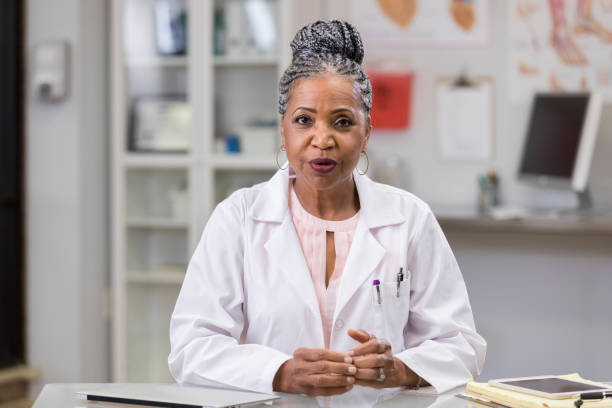 Point of view of patient receiving news from physician In this point of view of a patient, a serious senior female doctor sits across a table and shares information with her hands together. lab coat stock pictures, royalty-free photos & images