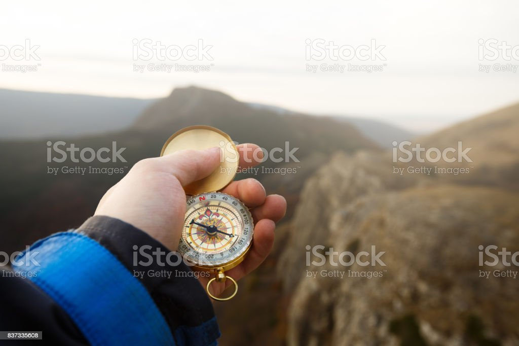 Point of view photo of explorer man searching direction with golden compass in his hand with autumn mountains background stock photo
