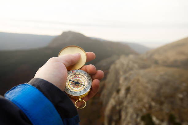 Point of view photo of explorer man searching direction with golden compass in his hand with autumn mountains background Point of view photo of explorer man searching direction with compass in his hand with blurred autumn mountains background explorer stock pictures, royalty-free photos & images