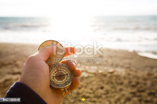 istock Point of view photo of man holding compass in the hand on the sea and beach background 840166848