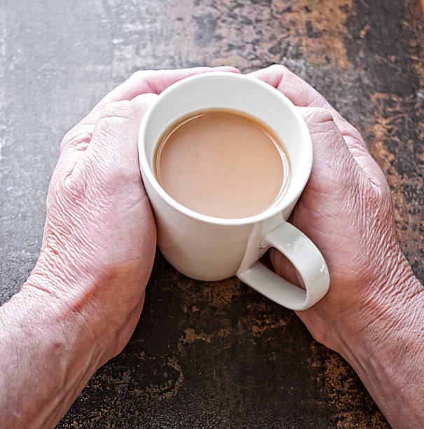 Point of View Senior Mans Hands with Coffee or Tea. stock photo