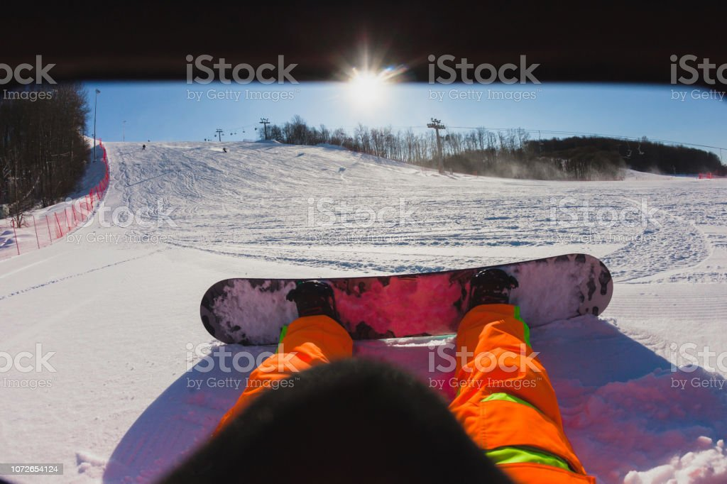 Point of view shot of a male snowboarder sitting on the snow stock photo