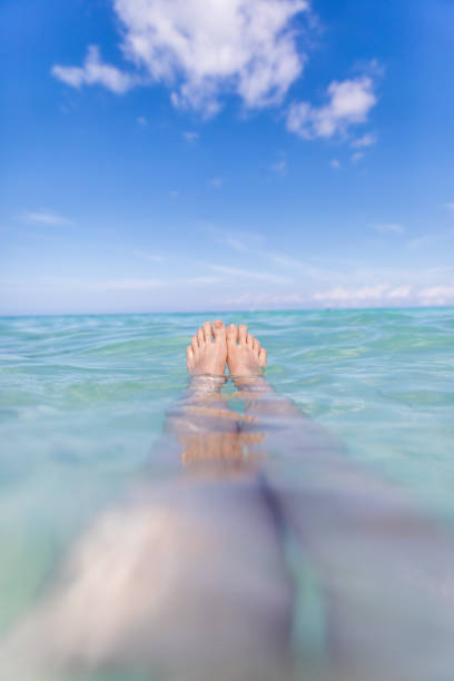 point of view woman feet floating on sea water - woman leg beach pov stock photos and pictures