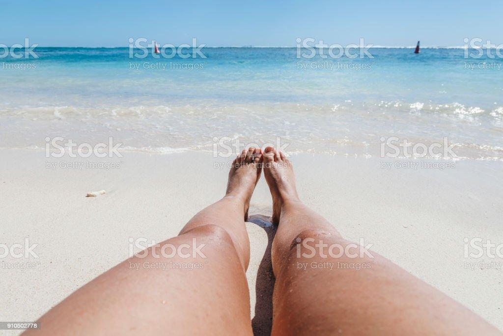 Standpunkt aus betrachtet, sieht junge Frau am Horizont sitzen auf einem Strand von Mauritius im Sommer – Foto