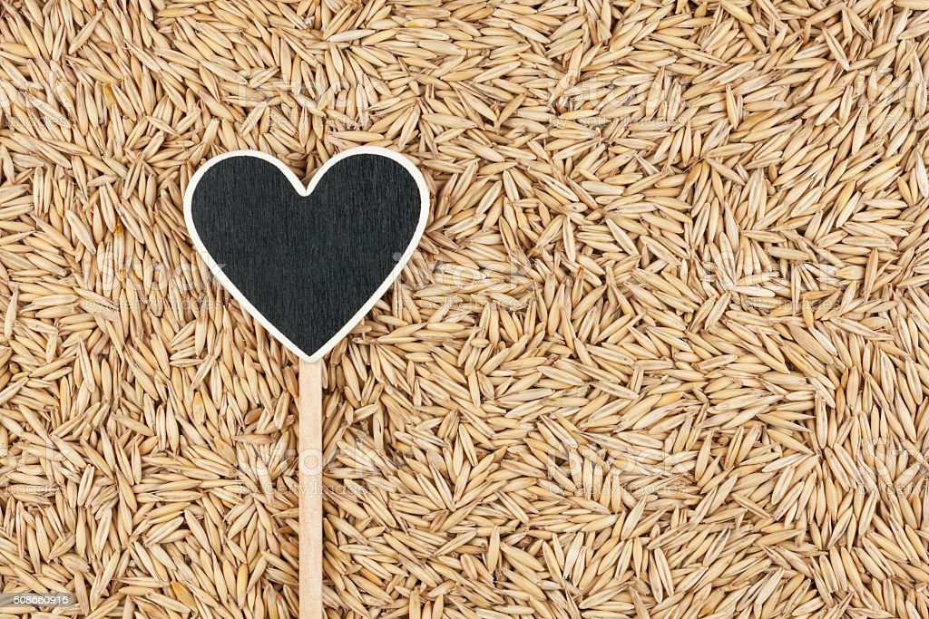 Pointer in the form of heart lies on oats grains stock photo
