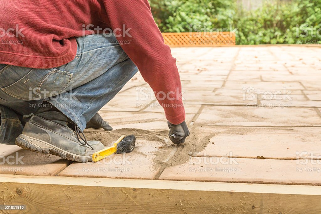 Pointing a patio with dry grouting cement grouting mix stock photo