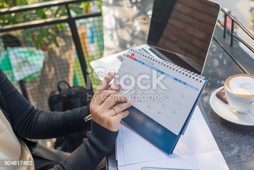istock Pointing on calendar by pen to remind about the meeting 504617452