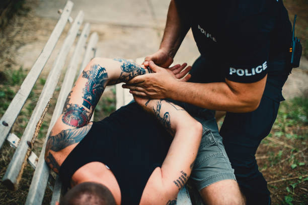 Pointing to the criminal Police putting handcuffs on a man arrest stock pictures, royalty-free photos & images