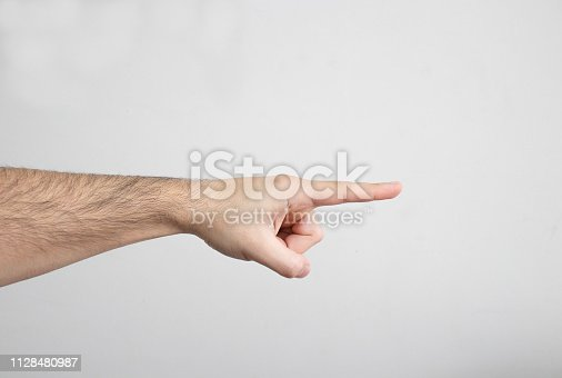 An image of a male hand who is pointing somewhere with his Index Finger.