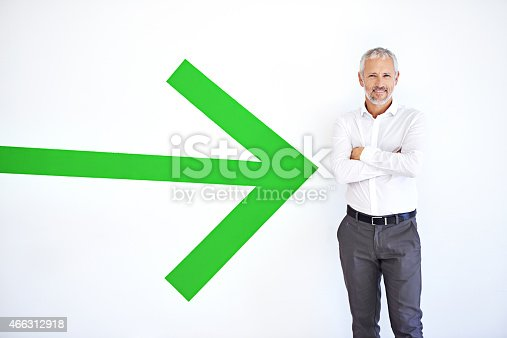 A mature businessman standing against a white background with a large green arrow pointing at him