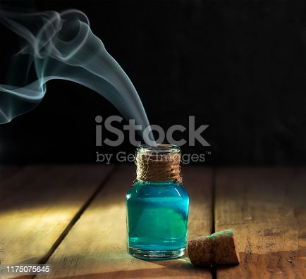 Poison with smoke in magic bottle on black and wooden background. Selective focus.