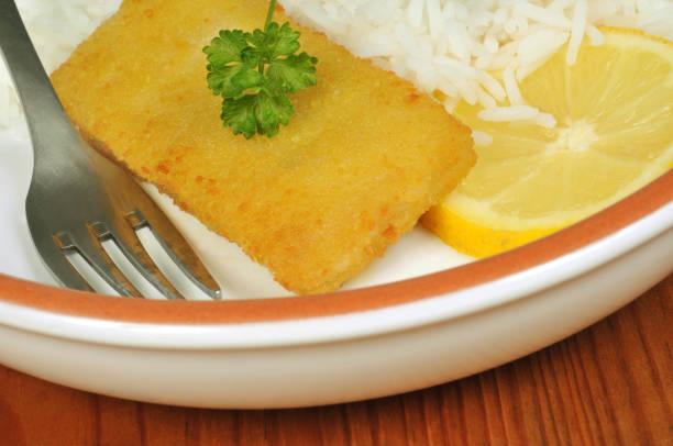 Poisson pané avec du riz et une rondelle de citron Poisson pané avec du riz et une rondelle de citron riz stock pictures, royalty-free photos & images