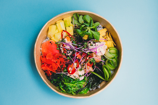 View tasty poke bowl with salmon, mango, ginger and rice on the blight blue flat lay - traditional Asian and Hawaiian street food