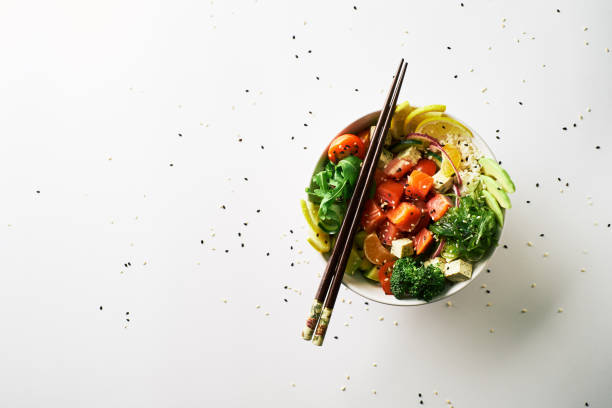 poke bowl with salmon, avocado, cucumber, arugula, broccoli, rice, carrot and sweet onions with chuka salad, chopsticks isolated over white background. top view poke bowl with salmon islated on white background. top view tuna seafood stock pictures, royalty-free photos & images
