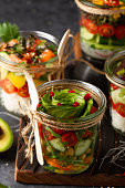 Poke salad with vegetables in a jar with fork on wooden rustic background. Close up. Healthy food