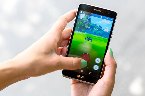 pokemon go game in a hand. zubat - mobile game stock photos and pictures