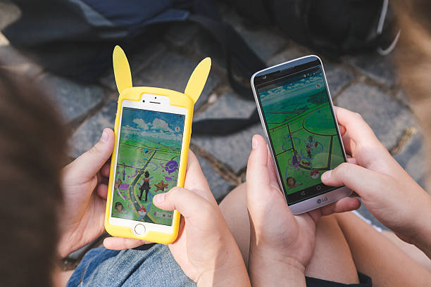 pokemon go gathering in rome - mobile game stock photos and pictures