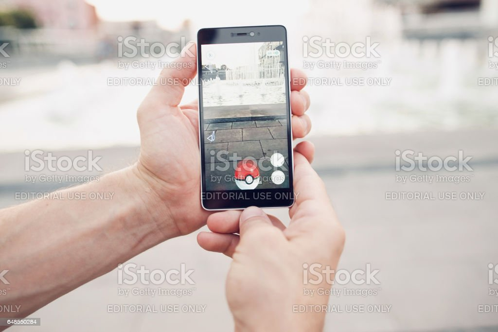 Pokemon Go playing smartphone game. Addicted. - Foto stock royalty-free di Afferrare