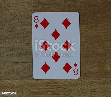 istock Poker card diamond eight on wooden background 915874034