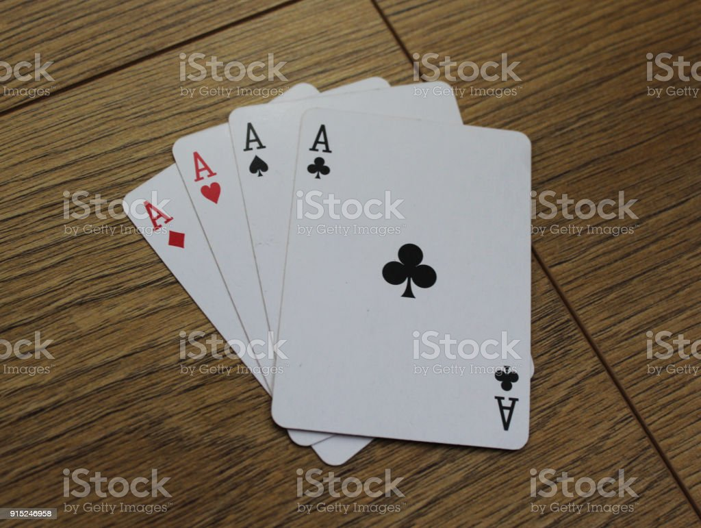 poker cards on a wooden backround, set of ace of clubs, diamonds, spades, and hearts – zdjęcie