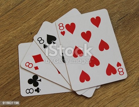 istock poker cards on a wooden backround, set of eight of clubs, diamonds, spades, and hearts 915601196