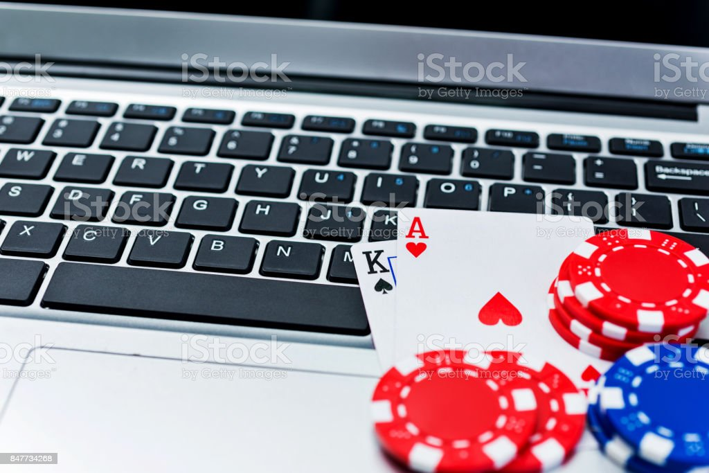 Poker chips and cards on computer keyboard stock photo