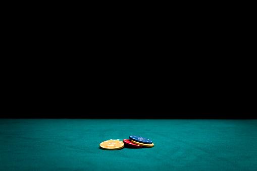 Poker chips on green felt casino table