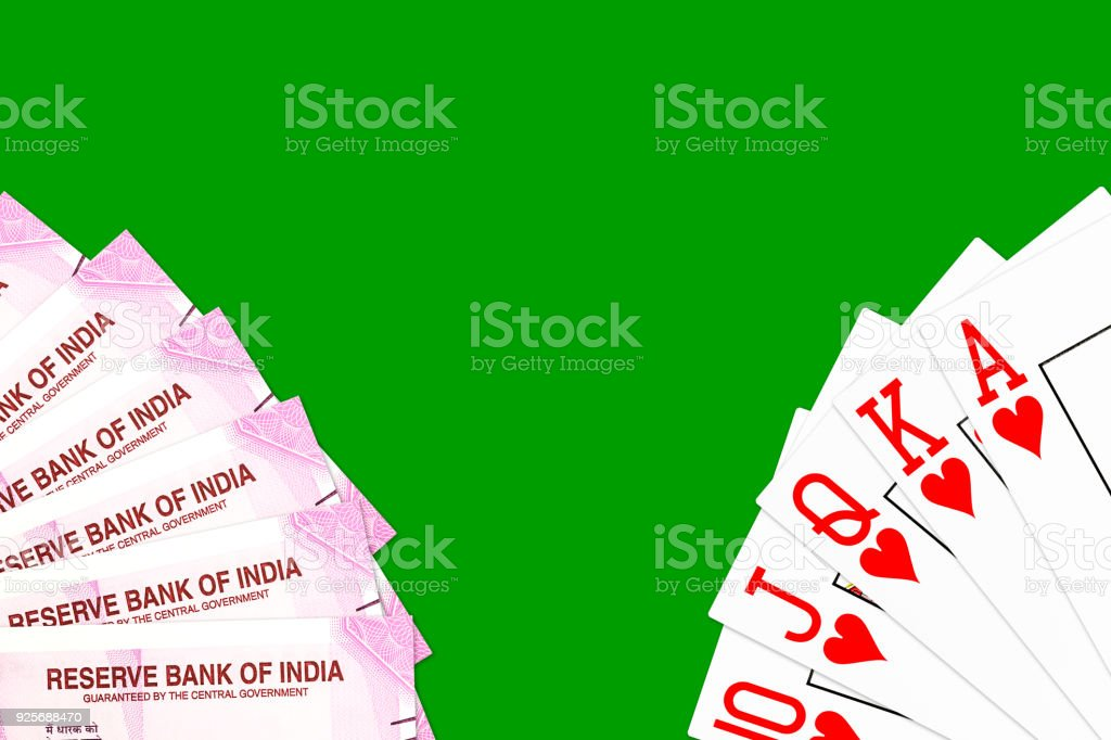 poker hand royal flush in hearts and 2000 indian rupee bank notes isolated on green background stock photo