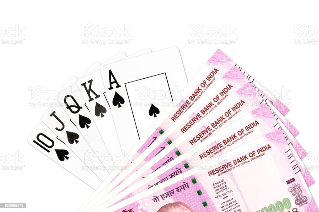 poker hand royal flush in spades and 2000 indian rupee bank notes isolated on white background stock photo