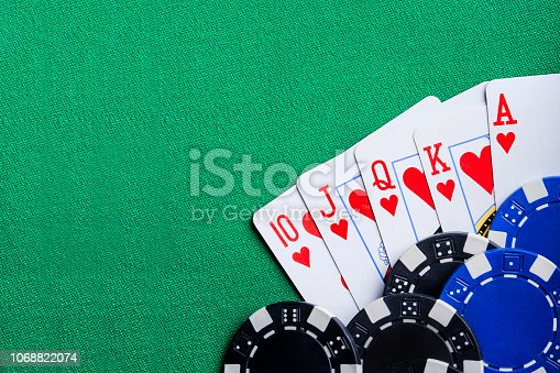 Playing Cards and Poker Chips with Royal Flush of hearts on them.