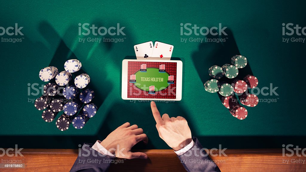 Poker player with digital tablet stock photo