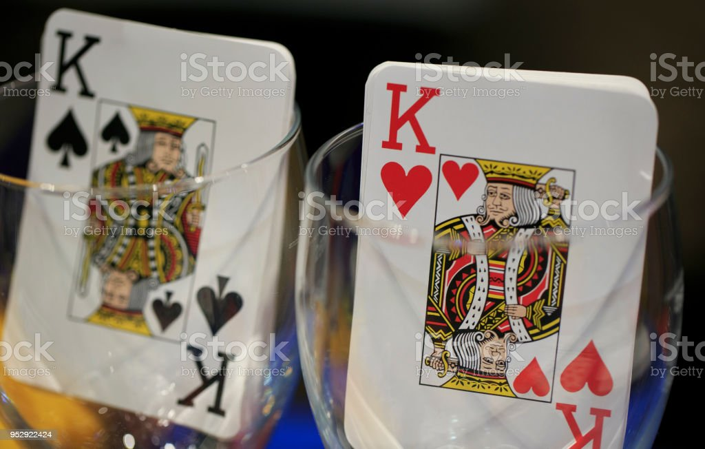 poker playing card inside a glass cup stock photo