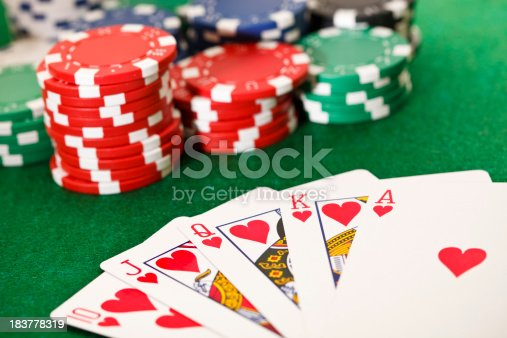 Poker cards showing the best poker hand -royal flush- and poker chips on a green card table. This is an exclusive image and it can only be found in iStockphoto.