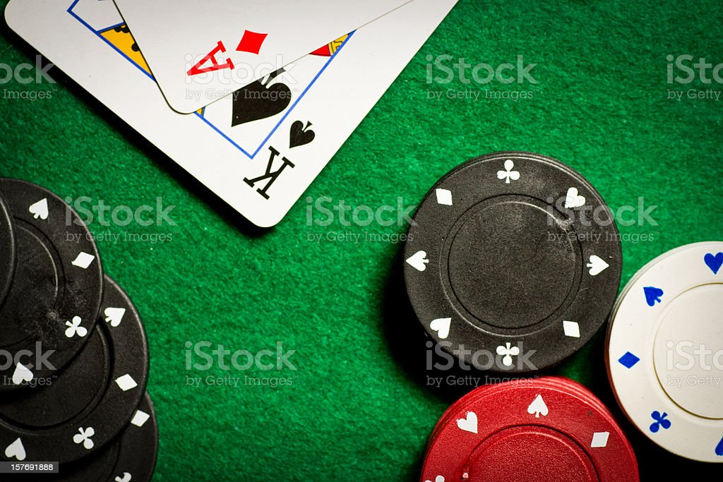 Poker table with gambling chips and two cards from above stock photo