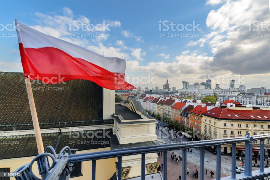 Poland Flag in Blue Sky and Warsaw in background