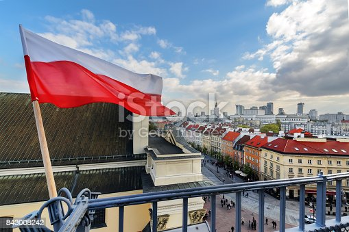 istock Poland Flag in Blue Sky and Warsaw in background 843008242