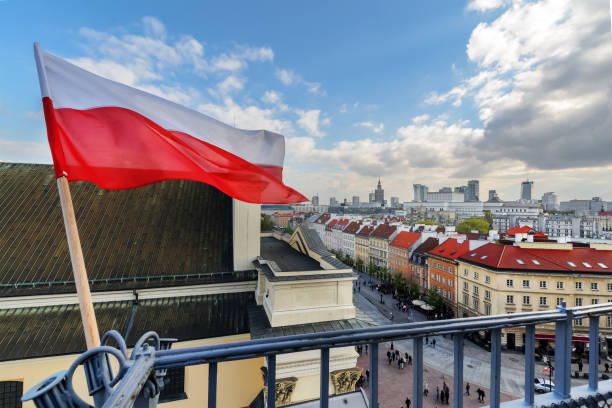 poland flag in blue sky and warsaw in background - poland stock photos and pictures
