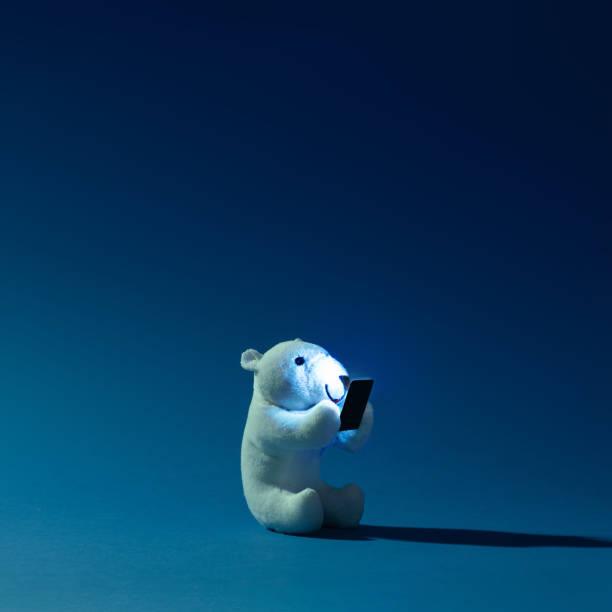 夜背景に携帯電話とホッキョクグマのおもちゃ。 - クマ ストックフォトと画像