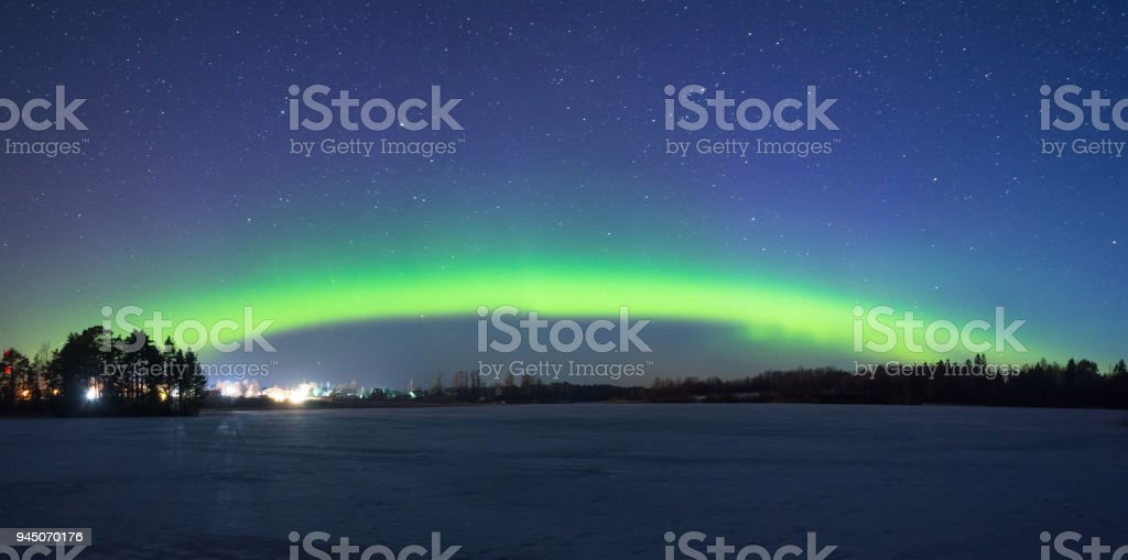 Polar northen lights aurora borealis at night in the starry sky above the lake with the island and the silhouette of the trees by the forest. Glowing arc over the horizon, panorama. stock photo