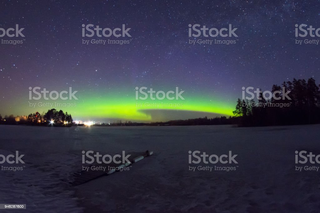 Polar northen lights aurora borealis at night in the starry sky above the lake with the island and the silhouette of the trees by the forest. Glowing arc over the horizon. stock photo