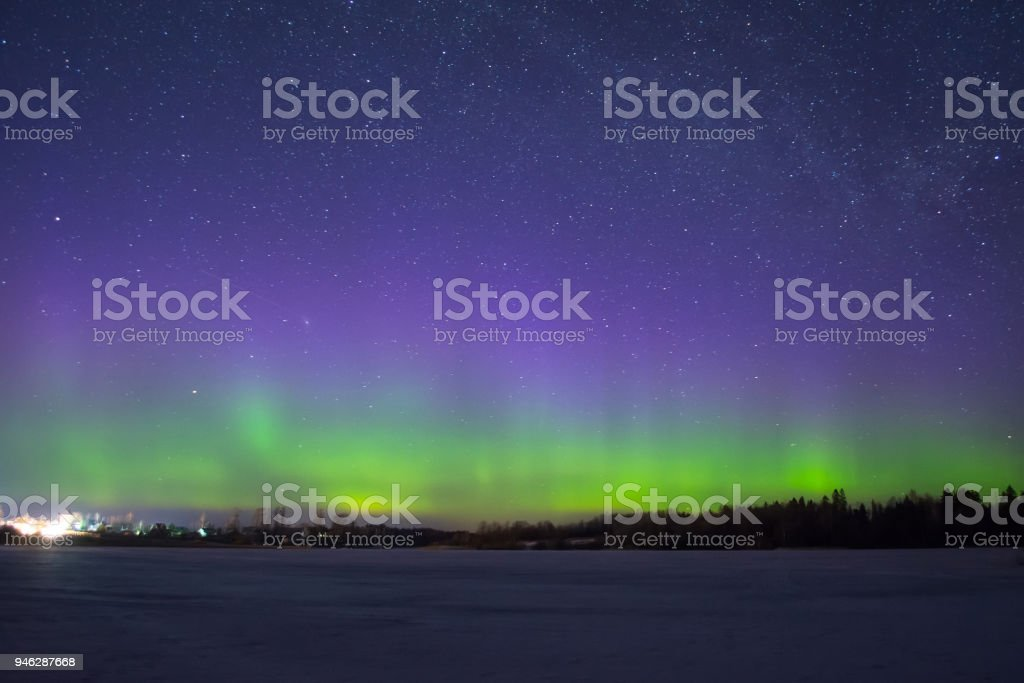 Polar northen lights aurora borealis at night in the starry sky above the lake with the island and the silhouette trees by the forest on horizon. stock photo