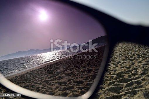 Photo shows a sandy beach with the sun high in the sky, through a sunglasses's lens.