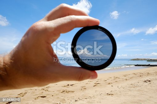 istock polarizing filter hold against the beach giving clarity. 912435212