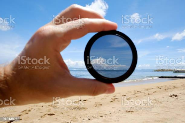 Polarizing filter hold against the beach giving clarity picture id912435212?b=1&k=6&m=912435212&s=612x612&h=mq17d66vqxc1ibsxv7koimelpqbd2lt65gx8jccavyo=