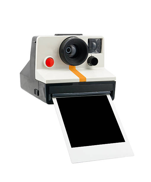 Polaroid camera printing a photograph on a white background stock photo