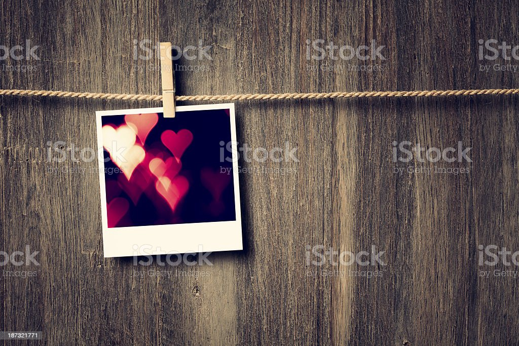Polaroid photo of heart bokeh on clothesline stock photo