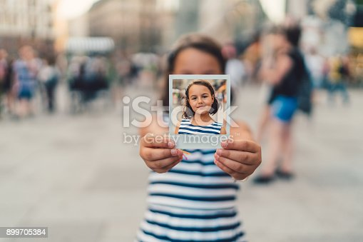 Cute girl showing polaroid self-portrait to the camera